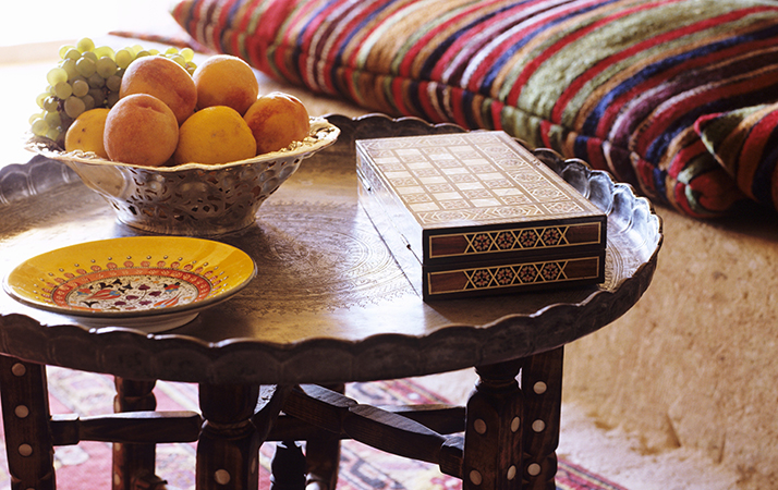 Fruit bowl on Oriental side table in front of striped cushions on platform