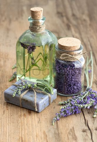 essential lavender oil, herbal soap and bath salt with fresh flowers on wooden background